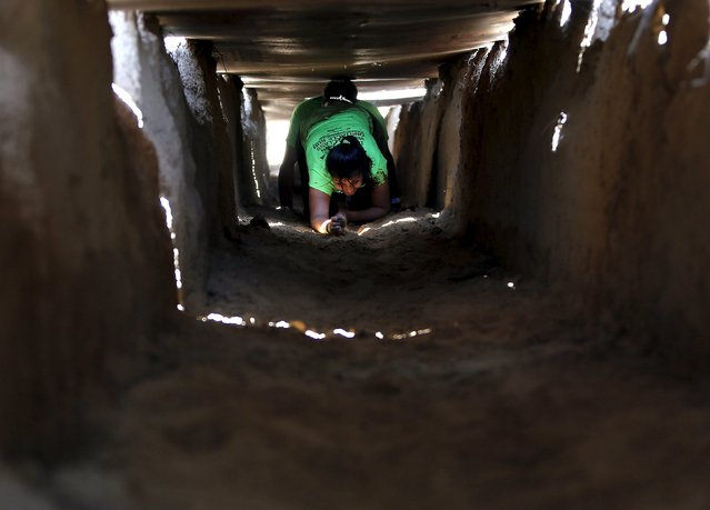 A competitor crawls through an obstacle course during the obstacle run at the Desi Warrior festival in Manesar in the northern Indian state of Haryana March 22, 2015. (Photo by Anindito Mukherjee/Reuters)