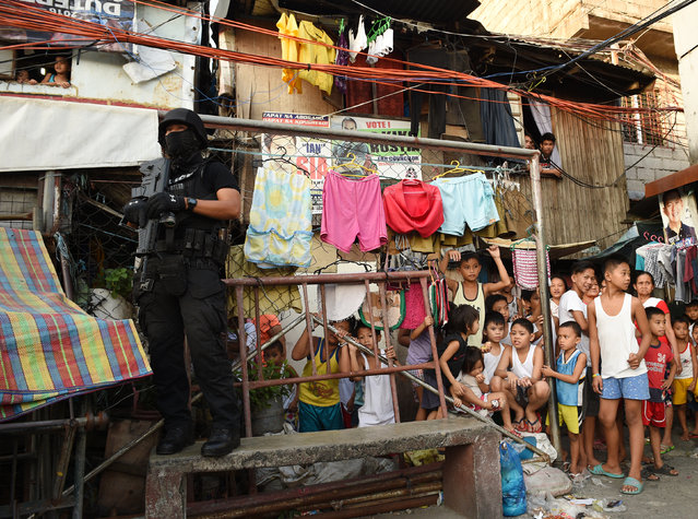 A member of the Special Weapons and Tactics (SWAT) team stands guard as residents look on during an anti-drug operation at an informal settlers area in Manila on November 9, 2016. Since President Rodrigo Duterte took office on June 30, his war on drugs and other crimes has claimed more than 4,100 lives, according to official figures. (Photo by Ted Aljibe/AFP Photo)