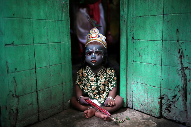 A child sits on a doorstep, dressed as Lord Krishna during Janmashtami festival, which marks the birth anniversary of Lord Krishna in Dhaka, Bangladesh, September 2, 2018. (Photo by Mohammad Ponir Hossain/Reuters)