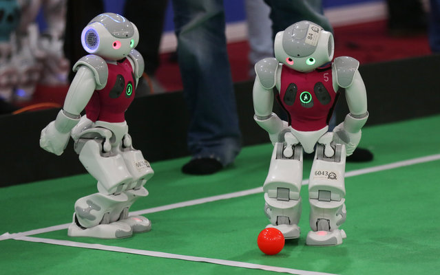 Robots from the German Nao Team Humboldt from the Berlin United University take part in a football game against Dutch Nao Team from the Van Amsterdam University, during the RoboCup Iran Open 2015, in Tehran, on April 8, 2015. (Photo by Atta Kenare/AFP Photo)