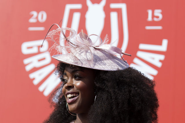 A spectator smiles during Aintree race meeting's Ladies Day the day before the Grand National horse race at Aintree Racecourse Liverpool, England, Friday, April 10, 2015. (Photo by Jon Super/AP Photo)