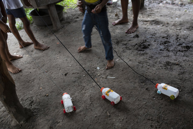 In this February 6, 2018 photo, children hold onto to their crafted toy trucks from plastic juice boxes with lids for wheels, in Puerto Lempira, Honduras. A sign of the poverty, boys craft toys from recycled material. For grown-ups, the only option they've found to deal with poverty is diving, no matter the risks. (Photo by Rodrigo Abd/AP Photo)