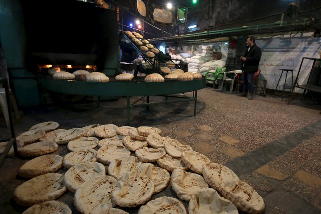 A man stands near bread cooling down after being baked inside a bakery in the rebel held al-Shaar neighborhood of Aleppo, Syria, February 10, 2016. (Photo by Abdalrhman Ismail/Reuters)