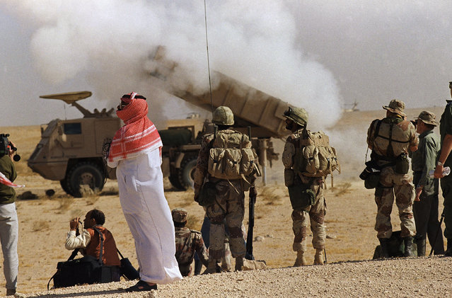 In this December 16, 1990 file photo, a Saudi Arabian official and Saudi soldiers watch a multiple rocket launch system near the Kuwaiti border in Saudi Arabia. (Photo by Bob Daugherty/AP Photo)