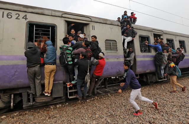 A boy runs to catch an overcrowded train near a railway station in Ghaziabad, on the outskirts of New Delhi, India, February 1, 2019. (Photo by Anushree Fadnavis/Reuters)