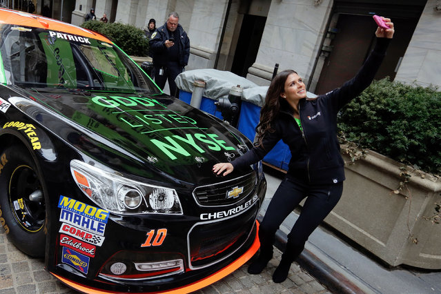 Race car driver Danica Patrick takes a selfie with her car in front of the New York Stock Exchange, before the Go Daddy IPO, Wednesday, April 1, 2015. (Photo by Richard Drew/AP Photo)