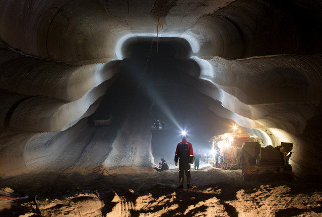 An employee uses the light from a head torch to illuminate the machine cut walls of a potash mine operated by OAO Uralkali in Berezniki, Russia, on Friday, August 23, 2013. (Photo by Andrey Rudakov/Bloomberg)