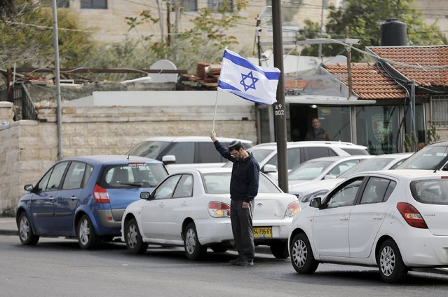 A man holds Israel's national flag as he stands still during the sounding of a two-minute siren marking Holocaust Remembrance Day in Jerusalem April 16, 2015. (Photo by Ammar Awad/Reuters)