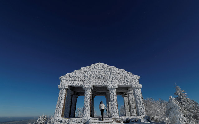 A woman visits the building that imitates a greco-roman temple which was built in 1869 on the summit of the Donon mountain as he enjoys a cold and sunny winter day in the Vosges mountains, in Granfontaine, near Strasbourg, France, January 19, 2017. (Photo by Christian Hartmann/Reuters)