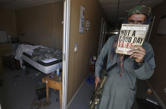 """A Taliban fighter shows a copy of the book """"Not a Good Day to Die"""" found inside a deserted US military camp at the airport in Kabul on September 14, 2021. (Photo by Karim Sahib/AFP Photo)"""