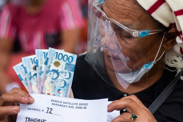 A woman receives cash assistance from the government following the imposition of two-week lockdown to prevent the spread of the coronavirus Delta variant, at an elementary school in Manila, Philippines, August 11, 2021. (Photo by Lisa Marie David/Reuters)