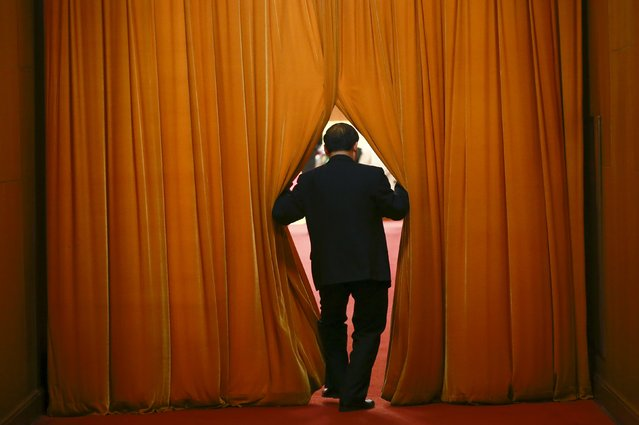 A delegate opens a curtain to walk through at the Great Hall of the People during the opening session of the National People's Congress (NPC) in Beijing, China, March 5, 2016. (Photo by Kim Kyung-hoon/Reuters)