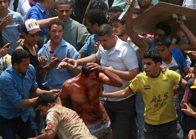 Egyptian protesters beat a man who they accused of attacking them in the Abbassiya district in Cairo on May 2, 2012. (Photo by Khaled Desouki/AFP Photo)
