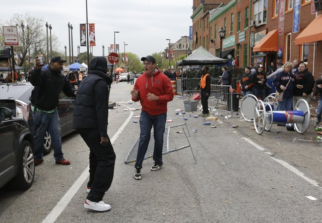 A bar patron, in red, confronts protestors outside of a bar near Oriole Park at Camden Yards after a rally for Freddie Gray, Saturday, April 25, 2015, in Baltimore. Gray died from spinal injuries about a week after he was arrested and transported in a police van. (Photo by Patrick Semansky/AP Photo)