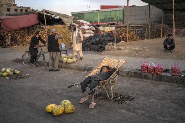 An Afghan boy sits on a wheelbarrow as he waits for customers at a street fruit and vegetable market in Kabul, Afghanistan, Wednesday, September 22, 2021. (Photo by Bernat Armangue/AP Photo)
