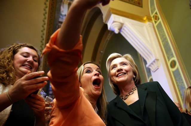 Democratic presidential hopeful and former Secretary of State Hillary Clinton (R) stops to take a selfie after meeting with members of the Iowa State legislature at the Iowa State Capital on April 15, 2015 in Des Moines, Iowa. (Photo by Justin Sullivan/Getty Images)