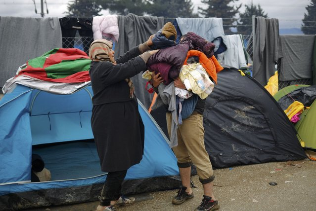 Migrants collect their belongings at a makeshift camp on the Greek-Macedonian border near the village of Idomeni, Greece March 10, 2016. (Photo by Stoyan Nenov/Reuters)
