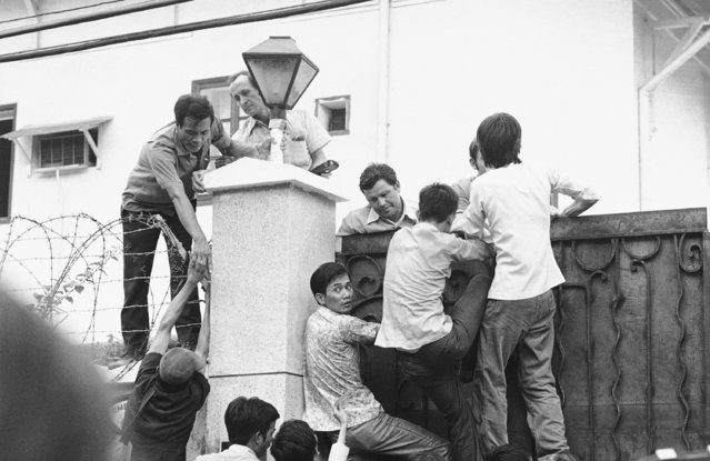 Vietnamese try to scale the high U.S. Embassy wall in desperate attempts to get aboard the evacuation flights in Saigon, May 1, 1975. (Photo by AP Photo)