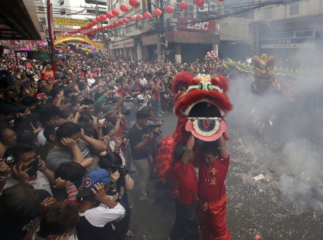 Firecrackers explode as dragon and lion dancers perform in front of a grocery store in celebration of Chinese New Year at Manila's Chinatown district of Binondo, Philippines, Friday, January 31, 2014. (Photo by Bullit Marquez/AP Photo)