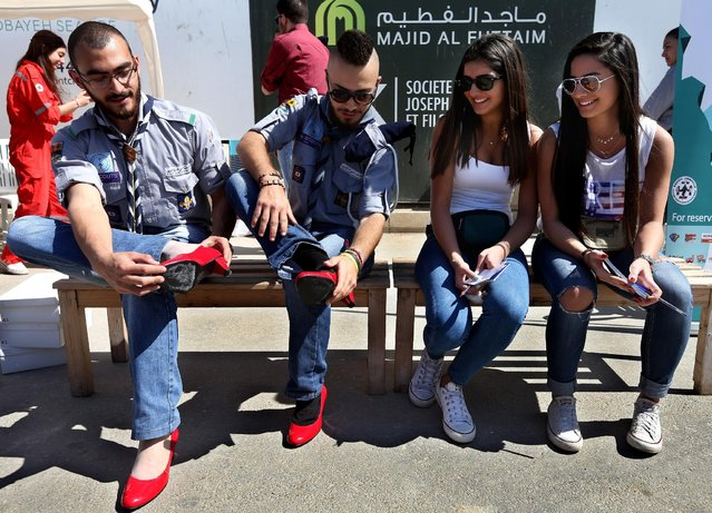 "Lebanese girls look at scouts as they wear high heels during an event called ""Walk a Mile in Her Shoes"", aiming to raise awareness on violence against women, in Dbayeh north of Beirut, Lebanon, Sunday, April 26, 2015. Lebanese men walked in red  high heels to call for an end to rape, sexual assault and gender violence. Civil rights activists say that an average of one woman is killed every month in Lebanon by her husband and that thousands of others are subjected to physical or verbal abuse. (Photo by Hussein Malla/AP Photo)"