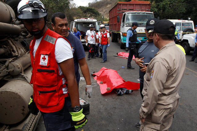 Rescue workers and members of the Red Cross stand next to a dead body after a crash between a bus and a truck on the outskirts of Tegucigalpa, Honduras, February 5, 2017. (Photo by Jorge Cabrera/Reuters)