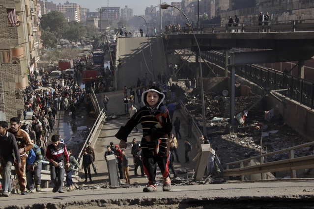 Residents stand on a bridge which collapsed in el-Marg, a suburb northeast of Cairo, Egypt, Tuesday, February 11, 2014. Egypt's state news agency says one policeman killed when an overpass crumbled after a fire broke in slums underneath in eastern Cairo. Egypt's state news agency says an overpass in eastern Cairo collapsed after a fire broke out in a slum settlement underneath it. The collapse killed a policeman. (Photo by Aly Hazzaa/El Shorouk/AP Photo)