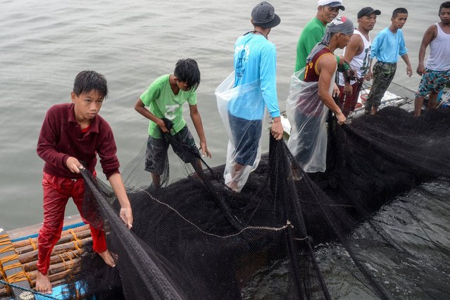 """In this photo taken on March 16, 2019, 13-year-old Reymark Cavesirano helps crew members with their nets onboard a fishing boat anchored at the mouth of Manila Bay off Navotas City in suburban Manila. """"My back usually aches from paddling but I cannot stop. I have to continue because we need to eat"""", he says. (Photo by Ted Aljibe/AFP Photo)"""