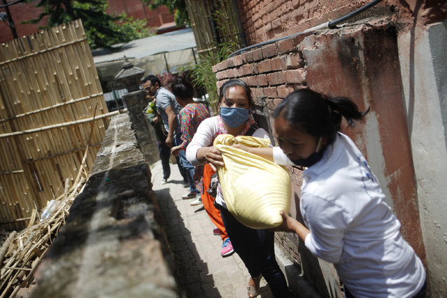 In this Tuesday, May 5, 2015 photo, Nepalese volunteers form a chain to load food and relief material collected by two Portuguese men onto a vehicle, for distribution among the earthquake affected in Kathmandu, Nepal. Using funds pledged through a Facebook appeal, two Portuguese men Pedro Queiros and Lourenco Macedo Santos are taking food and bedding to needy Nepalis made homeless by the magnitude 7.8 earthquake that struck just outside Kathmandu shortly before noon on April 25. (Photo by Niranjan Shrestha/AP Photo)