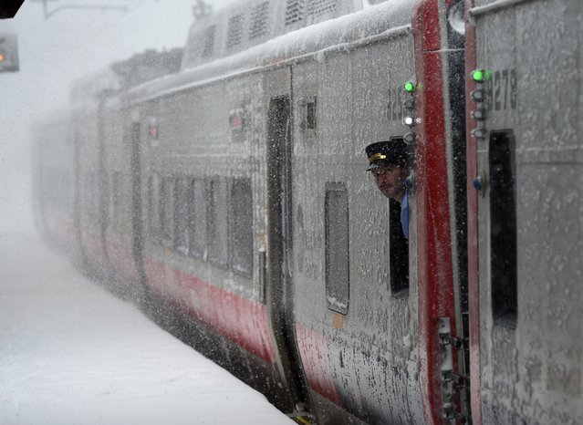 A train conductorlooks at the snow at the Metro North Greenwich train station on February 9, 2017 as  winter storms hit the area in Greenwich, Connecticut. (Photo by Timothy A. Clary/AFP Photo)