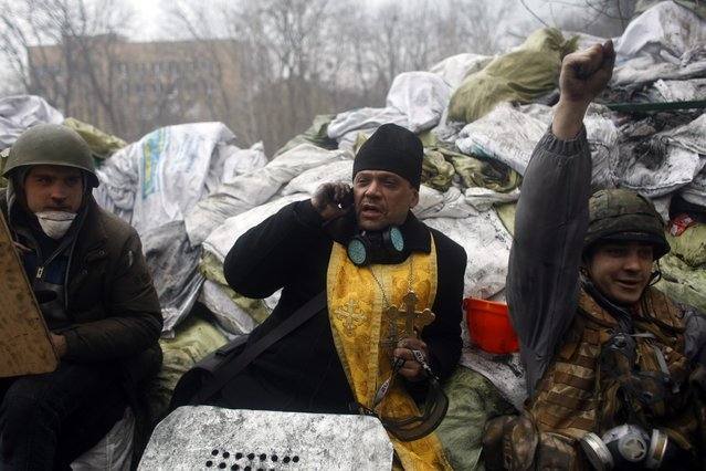 An Orthodox priest talks on the phone as anti-government protesters pause on a barricade on the outskirts of Independence Square in Kiev, Ukraine, Thursday, February 20, 2014. (Photo by Marko Drobnjakovic/AP Photo)