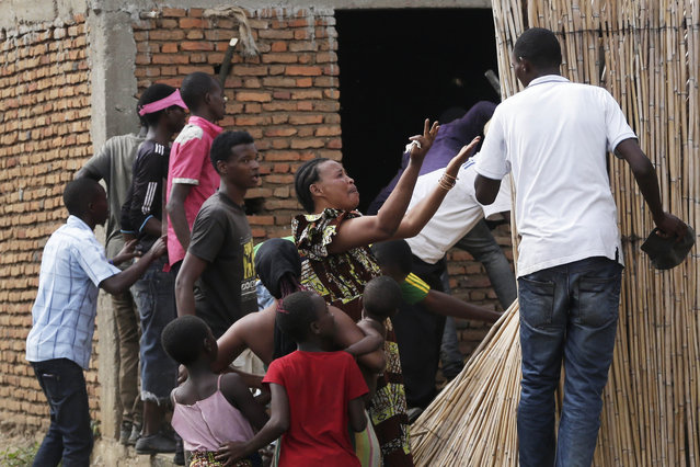 A crying woman argues with demonstrators who cornered a suspected member of the ruling party's Imbonerakure youth militia at his home in the Cibitoke district of Bujumbura, Burundi, Thursday May 7, 2015. Jean Claude Niyonzima, a suspected member of the ruling party's Imbonerakure youth militia, fled from his house into a sewer under a hail of stones thrown by a mob protesting against President Pierre Nkurunziza's decision to seek a third term in office. (Photo by Jerome Delay/AP Photo)