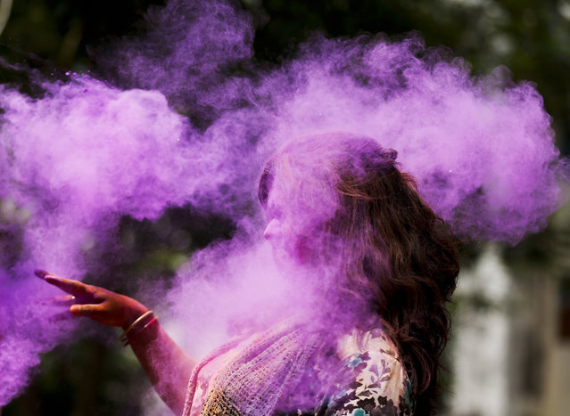 A Bangladeshi woman shuts her eyes as colored powder is smeared on her face during celebrations marking Holi, the Hindu festival of colors, in Dhaka, Bangladesh, Wednesday, March 23, 2016. The festival of colors, by painting each other in bright pigments, distributing sweets and squirting water at one another. The holiday celebrated mainly in India and Nepal marks the beginning of spring and the triumph of good over evil. (Photo by A.M. Ahad/AP Photo)