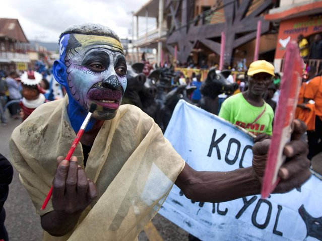 Jeanjean Robert, 53, pretends to paint his face during Carnival celebrations in Jacmel, Haiti, Sunday, February 23, 2014. People sporting painted faces or papier Mache masks paraded the streets of this town known for its arts to kick off Haiti's Carnival festivities. (Photo by Dieu Nalio Chery/AP Photo)