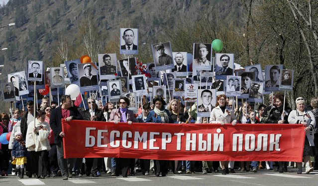 People hold pictures of World War Two soldiers as they take part in the Immortal Regiment march in the Siberian town of Divnogorsk near Krasnoyarsk, Russia, May 9, 2015. (Photo by Ilya Naymushin/Reuters)