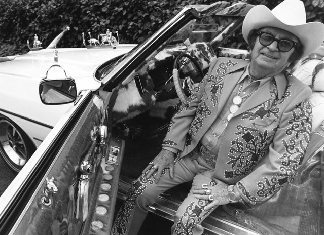 Nudie Cohen, known as Nudie (1902 – 1984), Russian-born costume designer for many country and western singers, sitting in his famous white Pontiac convertible, April 1971. The car has 14 guns mounted in varying positions, including Colt revolvers which work as door handles, arm-rests and gear levers. (Photo by Marti Coale/BIPs/Getty Images)