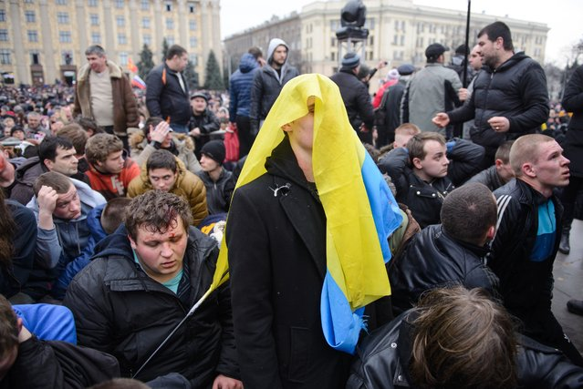 Pro-Western activists, one of them covering his head with a Ukrainian flag,  sit after being overpowered by pro-Russia activists after clashes at the local administration building in the northeastern city of Kharkiv, Ukraine, Saturday, March 1, 2014. Supporters of new Ukrainian authorities and pro-Russia demonstrators clashed in Kharkiv, a mostly Russian-speaking region in eastern Ukraine. (Photo by Olga Ivashchenko/AP Photo)
