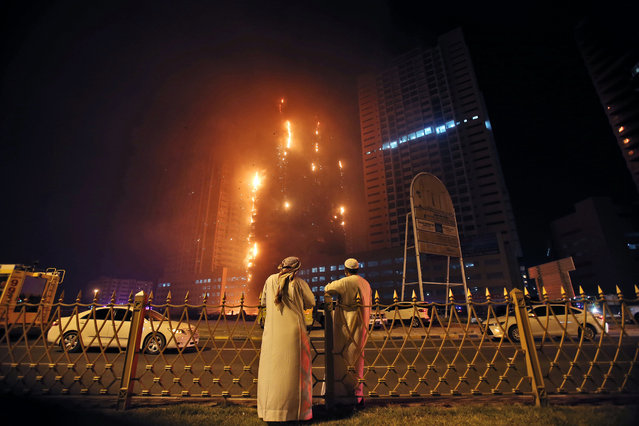 Two Emirati officials watch a high-rise building as a fire spreads up the side of the building in Ajman, United Arab Emirates, early Tuesday, March 29, 2016. Police in the United Arab Emirates city of Ajman confirmed the fire erupted at the high-rise tower, the latest in a series of skyscraper blazes in the Gulf nation, but gave no details of casualties. (Photo by Kamran Jebreili/AP Photo)
