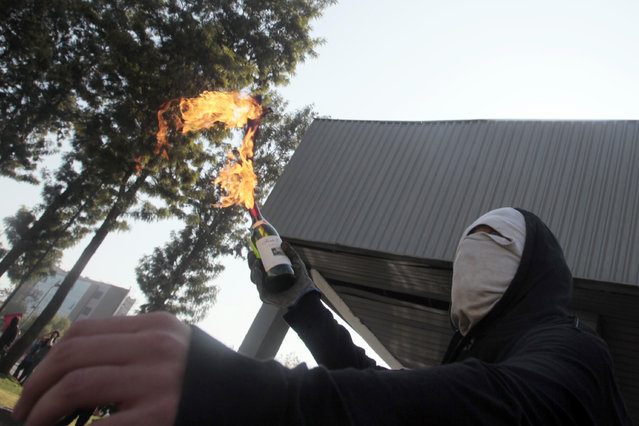 A masked demonstrator readies to throw a petrol bomb towards the police during a protest at the University of Santiago, in Santiago, Chile, Thursday, May 14, 2015. (Photo by Luis Hidalgo/AP Photo)