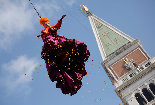 """A woman dressed as an """"angel"""" descends on Saint Mark's Square during the Venice Carnival, Italy February 19, 2017. (Photo by Alessandro Bianchi/Reuters)"""