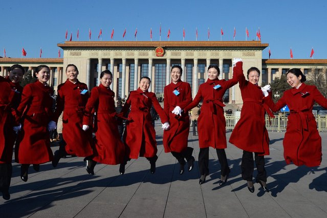 Chinese hostesses jump for photographers before the start of the National People's Congress (NPC) at the Great Hall of the People (back) in Beijing on March 5, 2014. China's annual show of political theater, the NPC is the first under the new Communist Party leadership and is facing intractable problems including endemic corruption, slowing economic growth and tensions with neighboring countries. (Photo by Mark Ralston/AFP Photo)