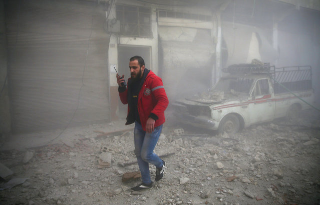 A Syrian Arab Red Crescent member walks at a site hit by airstrikes in the rebel held besieged Douma neighbourhood of Damascus, Syria February 19, 2017. (Photo by Bassam Khabieh/Reuters)
