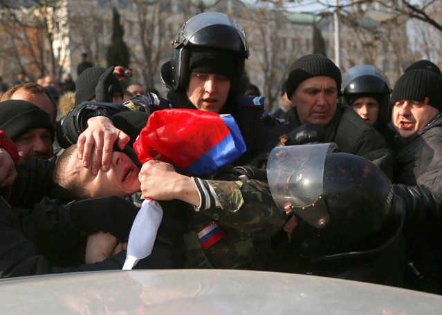 """Ukrainian police detain a demonstrator during a pro Russian rally in Donetsk, Ukraine, Sunday, March 9, 2014. As separatists in Crimea kept up pressure for unification with Moscow, Ukraine solemnly commemorated the 200th anniversary of the birth of its greatest poet, with the prime minister vowing not to give up """"a single centimeter"""" of Ukrainian territory. (Photo by Sergei Grits/AP Photo)"""