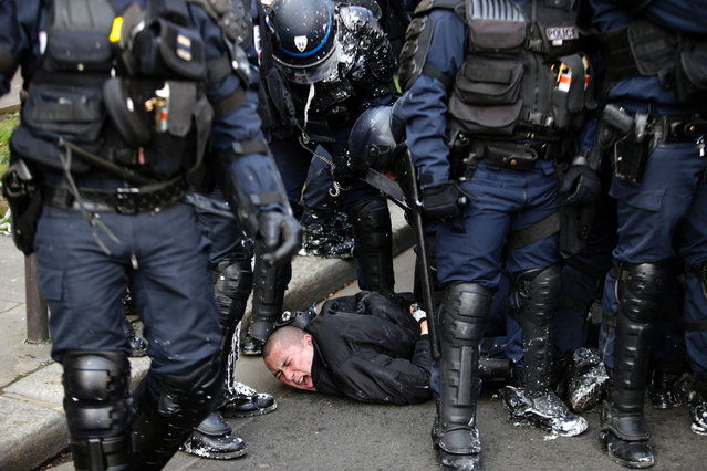 Anti-riot police officers arrest a man during clashes within a demonstration of high school students protesting against the government's planned labour reform, on April 5, 2016 in eastern Paris. (Photo by Kenzo Tribouillard/AFP Photo)