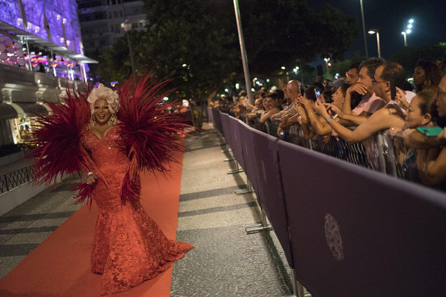 """A guest in a costume walks on the red carpet as she arrives to a traditional Carnival ball at the Copacabana Palace hotel in Rio de Janeiro, Brazil, Saturday, February 25, 2017. In stark contrast to the hundreds of hard-charging street parties across Rio that are open to anyone, the """"Baile do Copa"""" bills itself as a fairytale event where the country's elite can see and be seen in a hotel known for both opulence and a lengthy tradition of welcoming world leaders and stars. (Photo by Leo Correa/AP Photo)"""