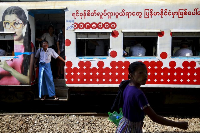 A woman walks pass near a train next people rides a train as they travel in Yangon on May 11, 2015. (Photo by Soe Zeya Tun/Reuters)