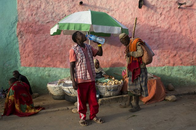 A man drinks from a water bottle in the old walled town of Harar in eastern Ethiopia, May 20, 2015. (Photo by Siegfried Modola/Reuters)