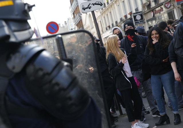 High school students face riot police officers during a protest in Paris, Thursday, April 14, 2016. Protesters across France are again marching to voice their anger at labor reforms being championed by the country's Socialist government. (Photo by Christophe Ena/AP Photo)