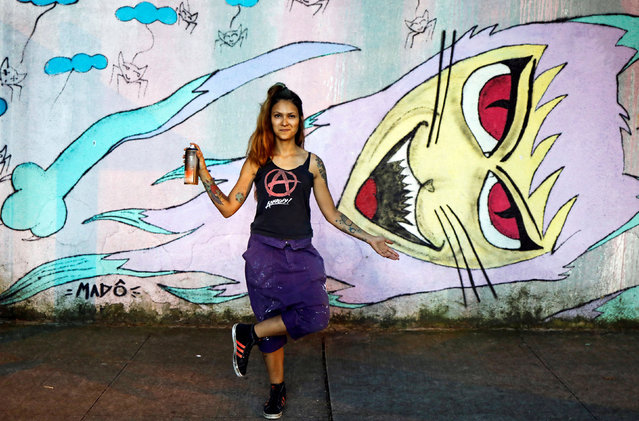 """Mado, 34, a Brazilian artist, poses for a photograph in front of her artwork at Vila Madalena neighbourhood in Sao Paulo, Brazil, February 23, 2017. """"Once a company did not want to hire me to paint a mural because they said that women could not carry the work material (paint boxes, ladders)"""", Mado said. """"I believe that things will only get better for all of us if men treat women equally"""". (Photo by Nacho Doce/Reuters)"""