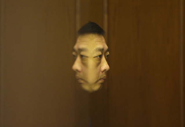 A hotel security personnel sits next to an entrance of a meeting hall, the venue of a routine briefing given by Malaysia's government and military representatives at Lido Hotel in Beijing March 23, 2014. (Photo by Jason Lee/Reuters)