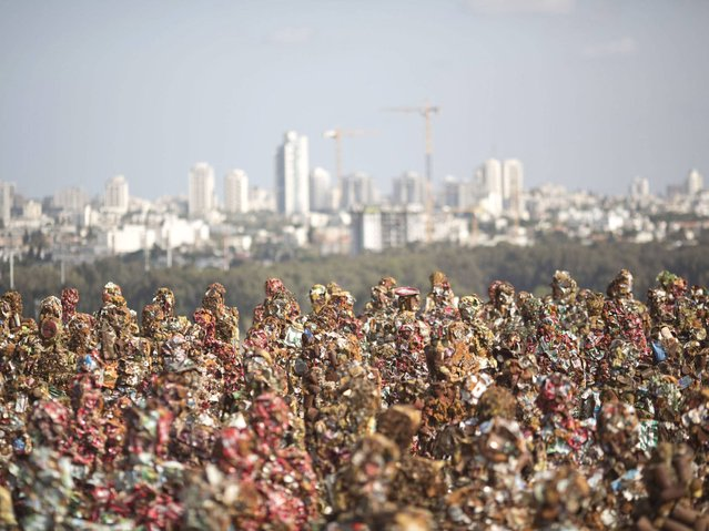 """The """"Trash People"""" an art exhibit of life-size figures made from 20 tons of recycled iron, glass, computer parts, cans and industrial waste, stands on Israel's Hiriya landfill near Tel Aviv. (Photo by Ariel Schalit/AP Photo)"""